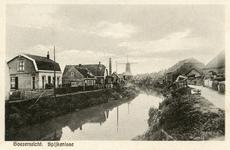 PB8910 De molen Nooitgedacht en het stoomgemaal langs de Vierambachtenboezem. Op de kade liggen bossen griendhout, ca. 1910