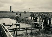 OV_HEINDIJK_91 Een groep mensen loopt vanaf de herbouwde Kogelgloeioven naar de steiger om op een boot te stappen; 1957