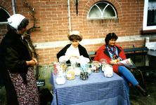 RO_DUINSTRAAT_20 Duinhuisje bij het museum De Duinhuisjes. Rechts een bezoekster, midden Joke Hendriks die snoep ...