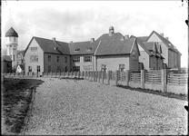 GN2051 De Hogere Burgerschool (HBS) met daarnaast de watertoren; ca. 1925