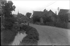 GN2452 Dorpsgezicht, links de kruidenierswinkel van A. Beijn. Links het café van Monster; ca. 1925