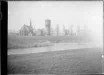 GN5128 Kijkje op de gereformeerde kerk, de watertoren en de katholieke kerk vanaf de wallen; ca. 1920