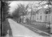 GN5131 Kijkje op de Zandweg waar een groep personen met een geit staan; ca. 1920