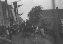 A1022 Feestelijke optocht met een paard met wagen en een muziekvaandel. Aan de gevels van de huizen hangen vlaggen.