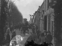 A1023 Feestelijke optocht met een paard met wagen en een muziekvaandel. Aan de gevels van de huizen hangen vlaggen.