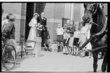 Bruidspaar Wagenmaker-Eecken verlaat de pastorie van de katholieke kerk aan het Grote Noord