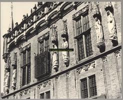 F001365 Beelden en laat-gotische ijzeren kooi aan de gevel van het Oude Raadhuis aan de Oudestraat, v.l.n.r. Karel de ...