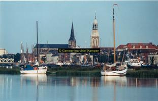 F005707 Zeilboten voor de kade, v.l.n.r. de Bovenkerk, de Nieuwe Toren en het Stadsarchief/Bibliotheek (met rode dak).