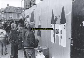 F005727 Beschildering van een omheining rond Buitenkade 2 en 4 door schoolleerlingen.