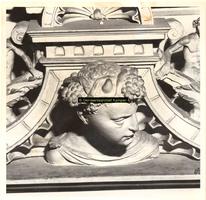F001544 Detailfoto van een mannenhoofd op de fries kijkend naar rechts, tussen het beeldje van de Hoop (Spes) en de ...