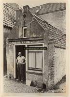 F001186 Een van de huisjes met de bewoner in de Schokkerbuurt, in 1859 verhuisden de bewoners van Schokland naar dit ...