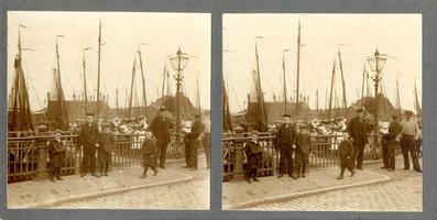 F012216 Een drietal schippers met veel schipperskinderen bij de Buitenhaven, op de achtergrond de gasfabriek.