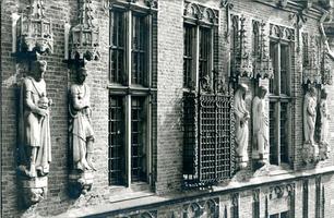 F004229 Beelden en laat-gotische ijzeren kooi aan de gevel van het Oude Raadhuis aan de Oudestraat, v.l.n.r. Karel de ...
