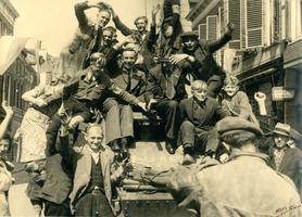 F004248 Kampenaren op een Canadese gevechtswagen in de Oudestraat, 17 april 1945. Een van hen is de heer G. Berghuijs.