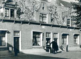 F004257 Bewoners op de binnenplaats van de Proveniershuisjes uit 1695 van de Verenigde Gasthuizen.
