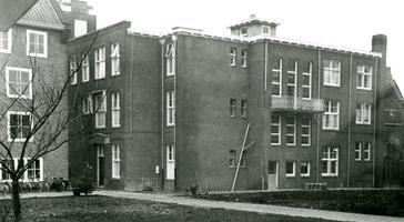F000528-1 Achterzijde en doorgang naar de binnenplaats van de ziekenzaal van de Gast- en Proveniershuizen uit 1930, ...