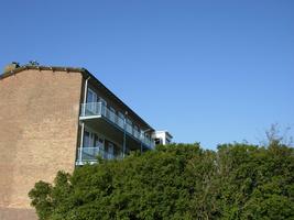 F013081 Vanuit de Dr. Damstraat een uitzicht op de achterzijde/balkonzijde van een flat aan de Rondweg in de periode ...