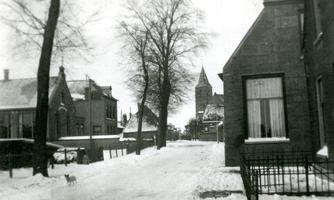 F009898 IJsselmuiden, de Dorpsweg in de winter van 1950, links de Chr. school, in het midden de toren van de N.H. kerk. ...