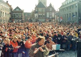 F013272 Kinderzang op de Nieuwe Markt ter ere van Koninginnendag.