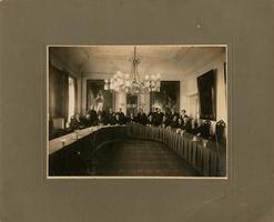F013190 Groepsfoto van burgemeester en bestuursleden in de Raadzaal van het gemeentehuis aan de Oudestraat. De man ...