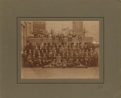 F013186 Groepsfoto van een groot aantal mannen aan de achterzijde van de Burgwalkerk, de man uiterst rechts (met ...