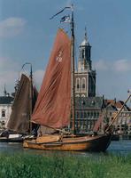F013213 Twee houten zeilschepen, platbodems, op de IJssel, waarvan één een botter. Met op de achtergrond, markant, de ...