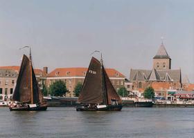F013214 Twee houten zeilschepen op de IJssel, met op de achtergrond de Van Heutszkazerne en rechts daarvan de Buitenkerk.