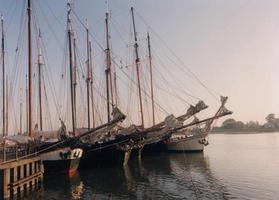 F013215 De steven en masten van vijf schepen van de bruine vloot van Kampen liggen naast elkaar aan de IJsselkade afgemeerd.