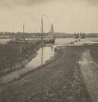 F000096 Een zeil-vrachtschip bevaart de IJssel, op de achtergrond het aanzicht van de stad met de Nieuwe Toren en de ...