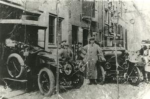 F005706 Achterzijde van de garage van J.W. Wolters (Oudestraat 40) aan de Hofstraat, de kleine man links, naast de ...