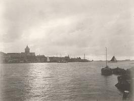 F000115 De IJssel stroomafwaarts, boven de daken van de woningen aan de IJsselkade steekt de toren van de Buitenkerk uit.