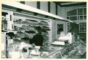F009209 De winkel van bakkerij Nijland, achter de toonbank de hulp en mevr. Nijland.