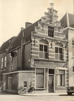 F000263 Hoekhuis met 17e eeuwse trapgevel, aan weerszijde boven de ramen van de beganegrond twee gebeeldhouwde koppen, ...