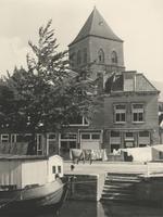 F000430 De Burgwal, op de voorgrond een woonark in de stadsgracht de Burgel, op de achtergrond de toren van de Buitenkerk.