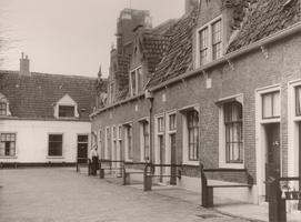 F000510 Huisjes met één van de bewoners op de binnenplaats van het Gast- en Proveniershuis aan de Burgwalzijde, nog net ...