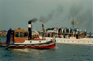 F011696 Een hele kleine sleepboot passeert het voormalig Koninklijk Jacht Piet Hein , het schip was het Nationale ...