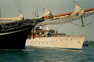 F011698 De driemaster de Vrijheid passeert hier de Piet Hein, het voormalig Koninklijk Jacht Piet Hein , het schip was ...