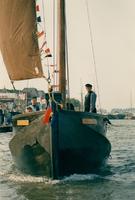F011692 Een oud zeilschip ter hoogte van het v. Heutzplein met de bemanning in klederdracht.