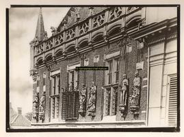 F001354 Beelden en laat-gotische ijzeren kooi aan de gevel van het Oude Raadhuis aan de Oudestraat, v.l.n.r. Karel de ...