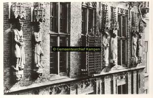 F001367 Beelden en laat-gotische ijzeren kooi aan de gevel van het Oude Raadhuis aan de Oudestraat, v.l.n.r. Karel de ...