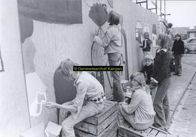 F005729 Beschildering van een omheining rond Buitenkade 2 en 4 door schoolleerlingen.