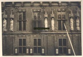 F001376 Beelden en laat-gotische ijzeren kooi aan de gevel van het Oude Raadhuis aan de Oudestraat, v.l.n.r. Karel de ...