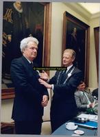 F004784 H.C. Kleemans toont de koninklijke onderscheiding van A. Hengeveld. Achter dhr. Kleemans zittend, O. Pol.
