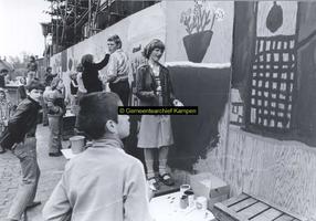 F005726 Beschildering van een omheining rond Buitenkade 2 en 4 door schoolleerlingen.
