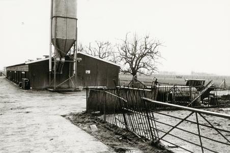 Houten varkensschuur met voedersilo achter de boerderij