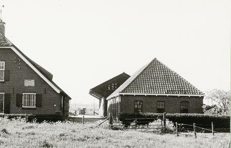 Rechter gedeelte van boerderij, rechts daarvan een schuur met schilddak, daarachter een open loods.