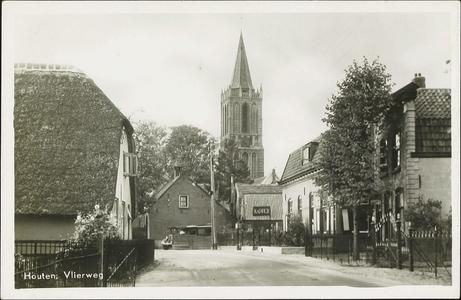 Gezicht op de toren van de nederlands-hervormde kerk vanaf de Vlierweg met rechts een gedeelte van het pand Vlierweg 3.
