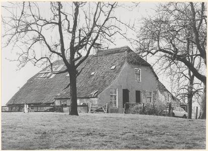 Boerderij Blokhoven. Gezicht op de voorgevel en linkerzijgevel van de boerderij met op de voorgrond hoogstam-fruitbomen.