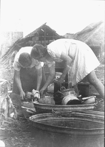 Washing up bowls and pans are prepared for the collection of food in Kampili Camp, 1945.<br/>NIOD 58208 <a class=uline href=http://www.beeldbankwo2.nl target=_blank>Beeldbank WO2</a>