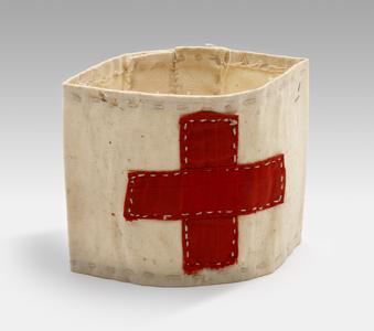 Een wit katoenen armband met daarop een rood katoenen kruis, bestemd voor een verpleger. De band behoorde aan A.F.R. De Ruyter De Wildt.<br/>NIOD Collectie 417-053